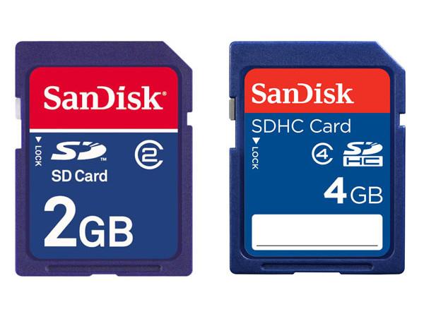 Karty pamięci Sandisk SD 2GB i SDHC 4GB. Pierwsza z nich posiada klasę szybkości 2, co oznacza minimalną prędkość zapisu na poziomie 2 MB/s. W przypadku drugiej karty szybkość gwarantowana to zapis na poziomie przynajmniej 4 MB/s. Karty pamięci o tych parametrach w zupełności wystarczą do naszych codziennych zastosowań.
